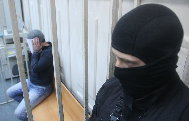 Anzor Gubashev (back), one of the suspects in the Boris Nemtsov murder case hides his face as he appears at Moscow's Basmanny District Court