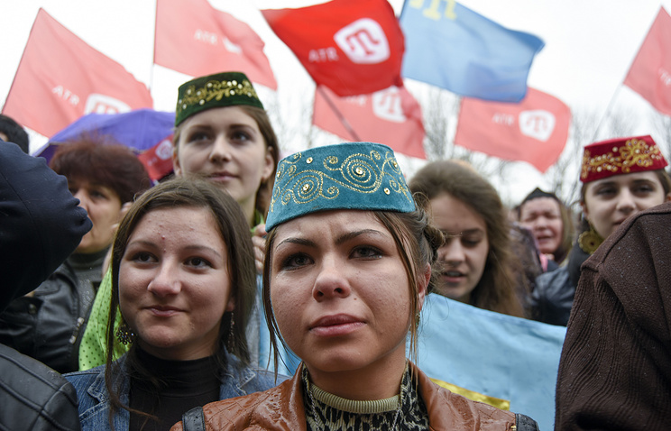 Crimean Tatars hold ATR TV station flags during a support rally in Simferopol, Crimea
