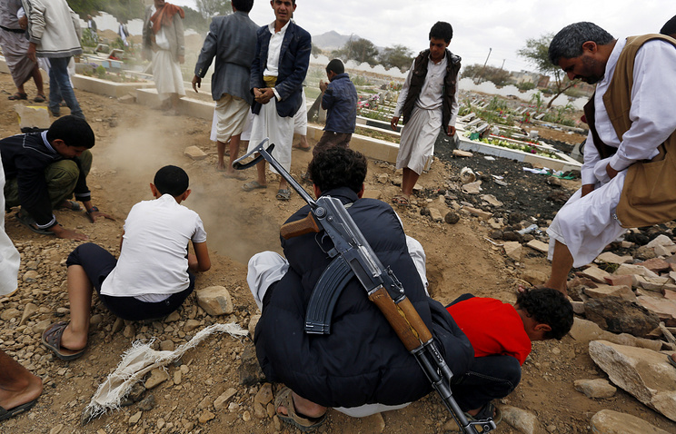 Houthi supporters bury the body of a comrade
