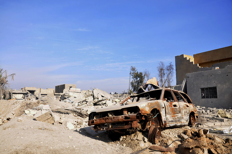 A burned out car lies amid damaged buildings in Ramadi, Iraq