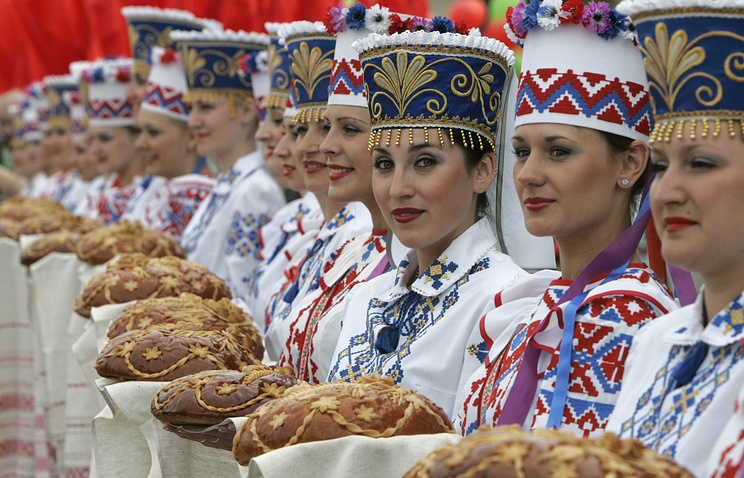 Women wearing Belarusian national dresses with traditional bread-and-salt