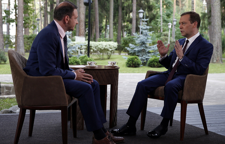 Russia's prime minister Dmitry Medvedev (R) gives an interview to Rossiya 1 journalist Sergei Brilev