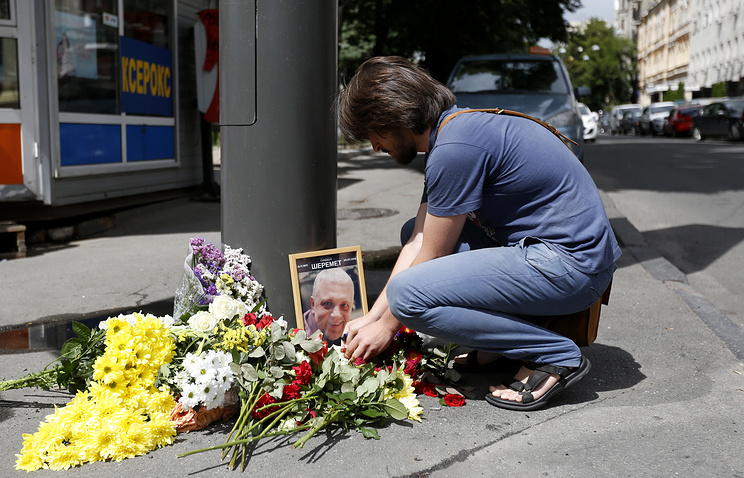 Portrait of Pavel Sheremet surrounded with flowers and candles at a place of his death in Kiev