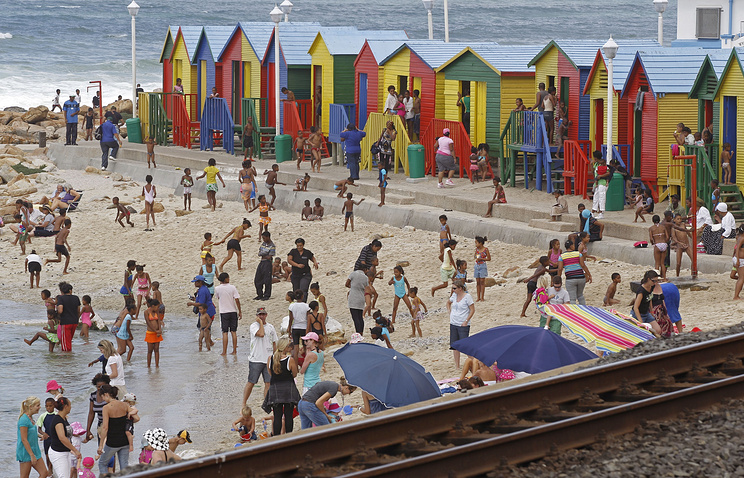 People play in the ocean on the outskirts of Cape Town, South Africa