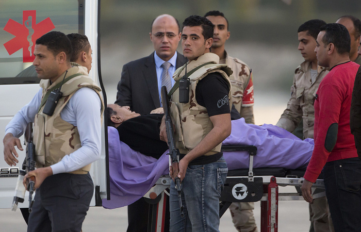 Egypt's former President Hosni Mubarak escorted by medical and security personnel