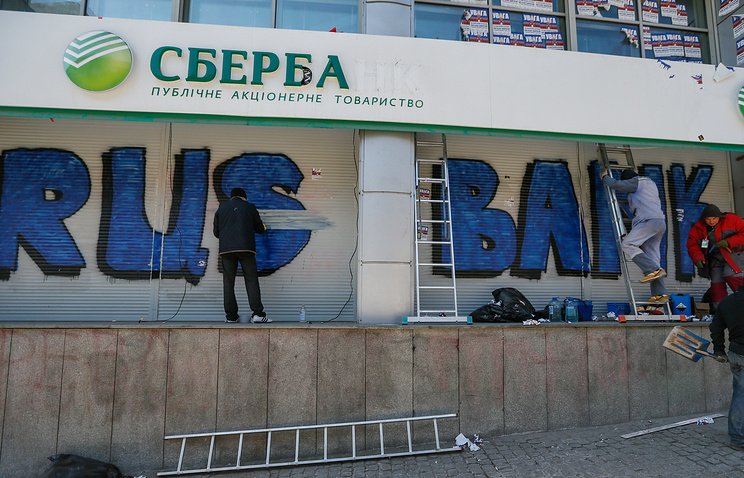 Ukrainian workers clean graffiti and dismantle the wall cordoning off the entrance to the office of Ukraine subsidiary of Sberbank in downtown Kiev