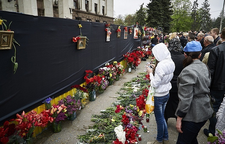 People laying flowers during an event commemorating victims of the Odessa tragedy