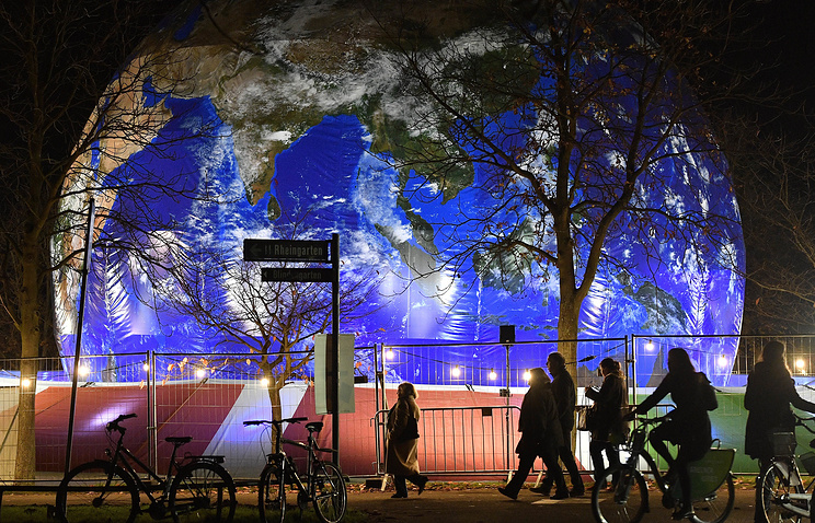 People pass the German pavilion in the shape of the earth during the COP 23 UN Climate Change Conference in Bonn