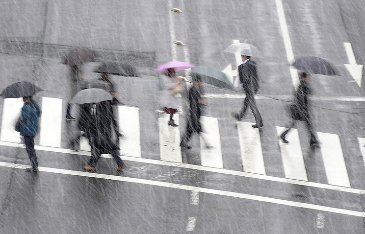 People walk under snow falling at a pedestrian crossing in Tokyo