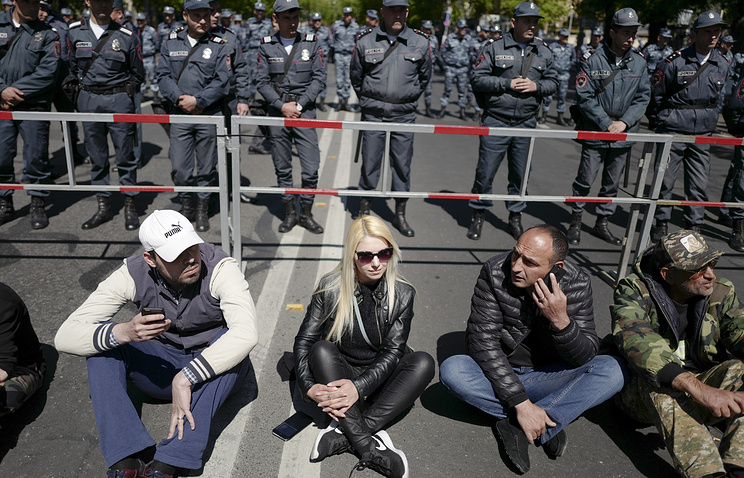 Opposition demonstrators sit in front of police line to protest the former president's shift into the prime minister's seat in Yerevan