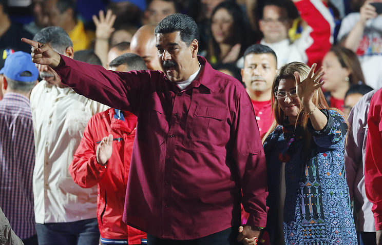 Venezuela's President Nicolas Maduro and his wife Cilia Flores wave to supporters at the presidential palace in Caracas