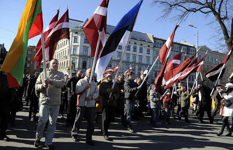 People march in a procession to the Freedom Monument to honor soldiers of the Waffen SS unit in Riga
